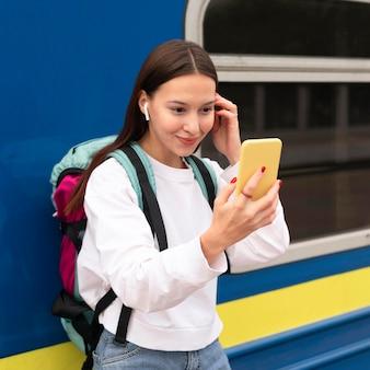 Leuk meisje bij het station die mobiele spiegel onderzoeken