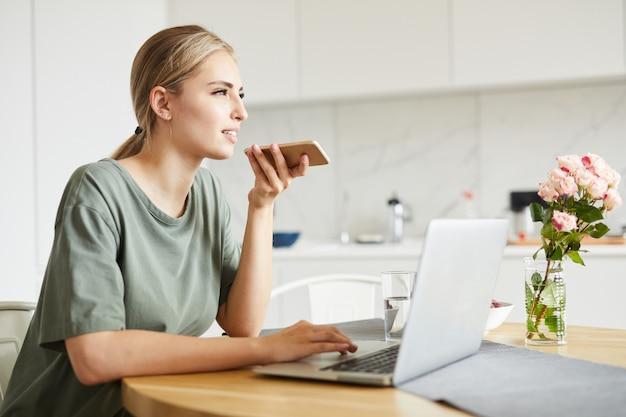 Leuk meisje browsen in het net tijdens het opnemen van voicemail op smartphone