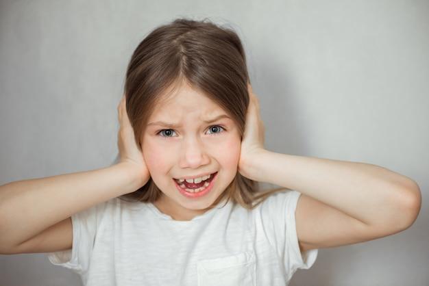 Leuk meisje dat aan hoofdpijn op grijze achtergrond lijdt