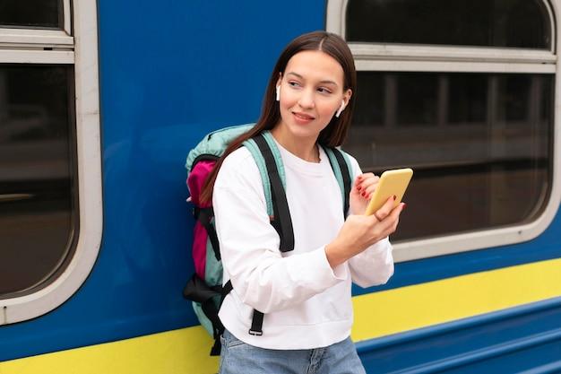 Leuk meisje dat bij het station mobiele telefoon houdt
