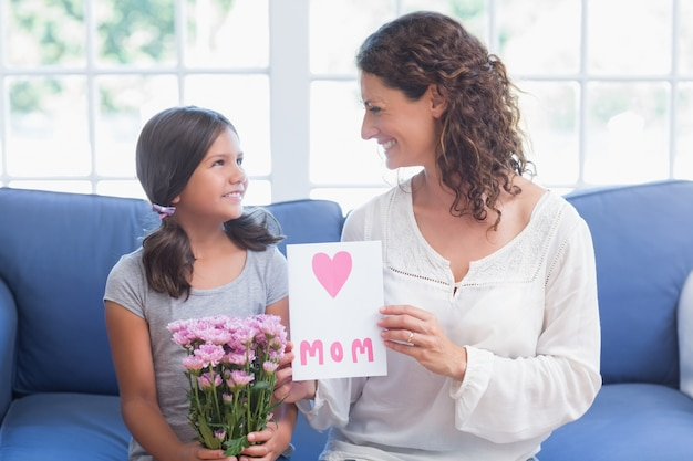 Leuk meisje dat bloemen en kaart aanbiedt aan haar moeder