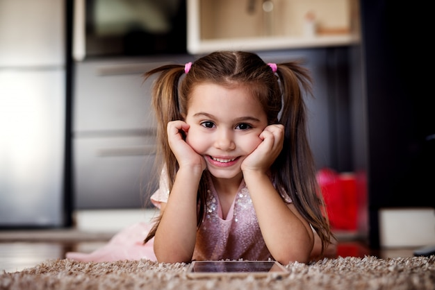 Leuk meisje dat camera bekijkt en tablet houdt. mooi kind portret.