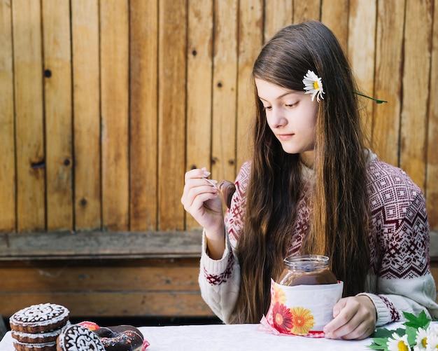 Leuk meisje dat chocolade eet die met lepel op kerstmis wordt uitgespreid