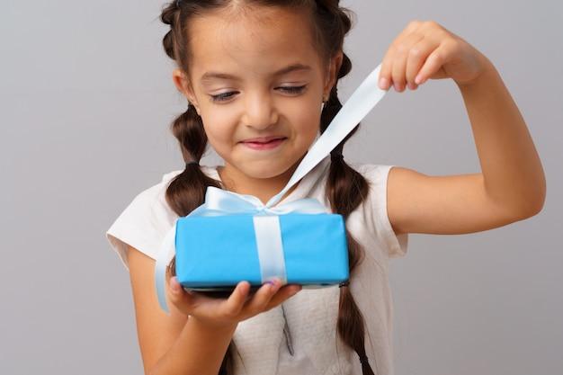 Leuk meisje dat een blauwe geschenkdoos in haar handen houdt