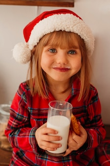 Leuk meisje dat een kerstmiskoekje en een glas melk houdt