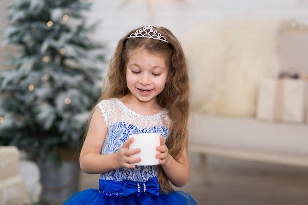 Leuk meisje dat een kunstmatige kaars in haar handen voor huisdecoratie houdt voor de kerstmisvakantie. kindvriendelijk landschap.