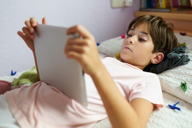 Leuk meisje dat een tabletcomputer in haar slaapkamer met behulp van