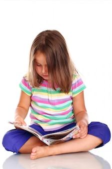 Leuk meisje dat een tijdschrift of een komisch boek leest