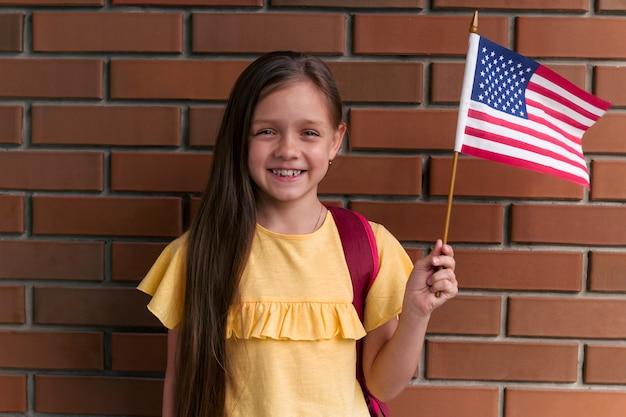 Leuk meisje dat en amerikaanse vlag glimlacht houdt status die zich tegen bakstenen muur bevindt