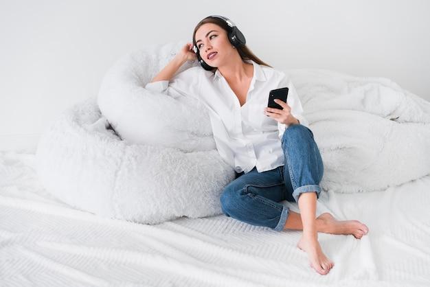 Leuk meisje dat in bed blijft en aan muziek luistert