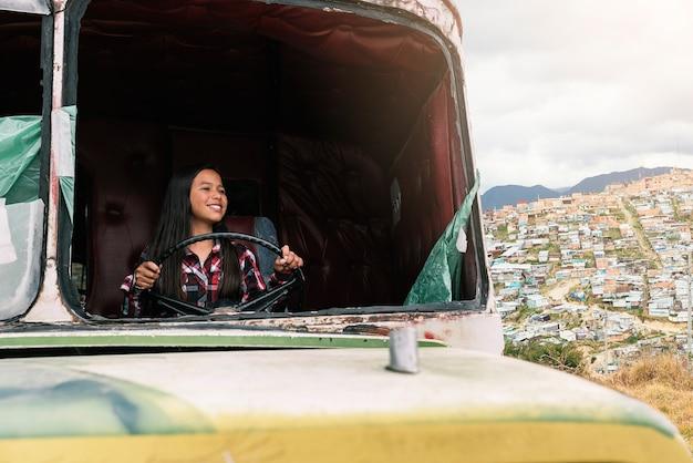 Leuk meisje dat in een verlaten vrachtwagen speelt. slecht zuigelingenconcept.