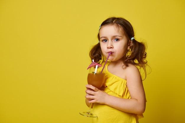 Leuk meisje dat in gele t-shirt een fruitcocktail van een rietje drinkt, dat op geel met exemplaarruimte wordt geïsoleerd.