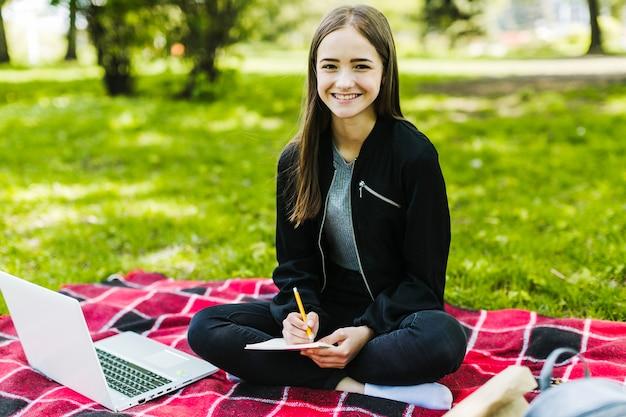 Leuk meisje dat in het park studeert