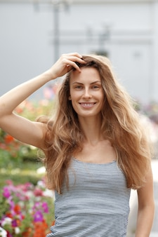 Leuk meisje dat langs de bloementuin loopt. gelukkige toerist met wind in haar haar.