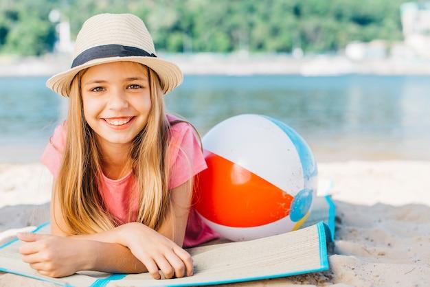 Leuk meisje dat met bal op kust glimlacht