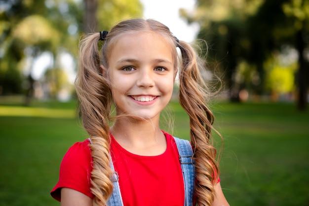 Leuk meisje dat met blond haar bij camera glimlacht
