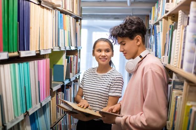 Leuk meisje dat met boeken haar klasgenoot met tablet bekijkt tijdens bespreking van huistoewijzing tussen boekenplanken in bibliotheek