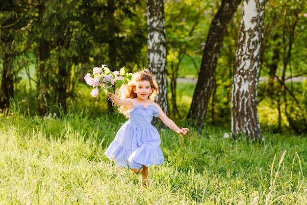 Leuk meisje dat met bos van bloemen loopt