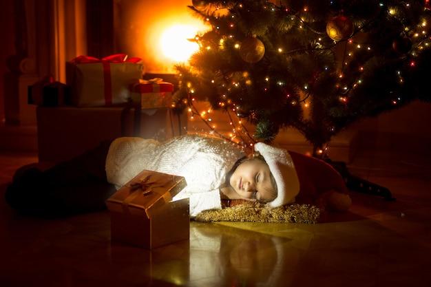 Leuk meisje dat onder de kerstboom ligt en in een gloeiende geschenkdoos kijkt