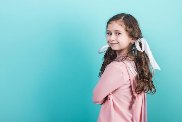 Leuk meisje dat op blauwe achtergrond glimlacht