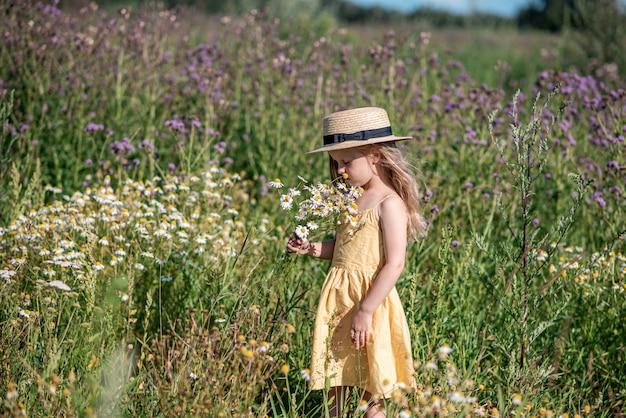 Leuk meisje dat op het bloemengebied loopt in gele kleding en hoed, de zomertijd