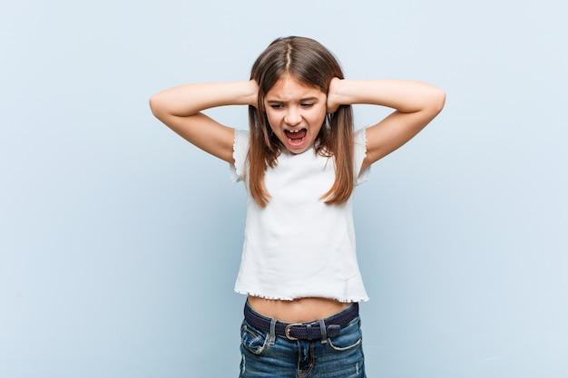 Leuk meisje dat oren behandelt met handen die niet te hard geluid proberen te horen