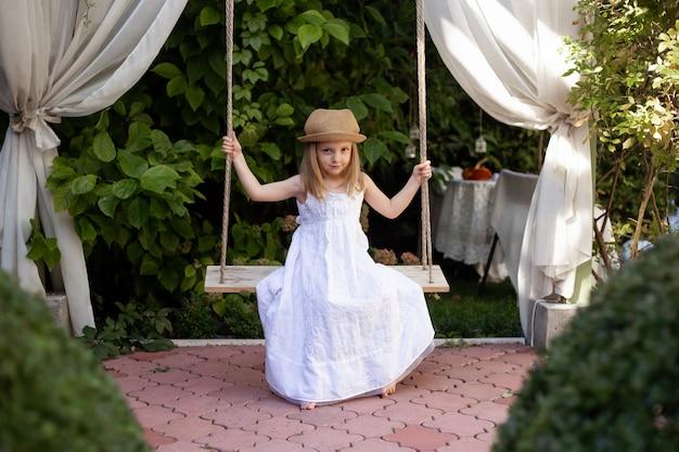 Leuk meisje dat pret op een schommeling in mooie de zomertuin heeft op warme en zonnige dag in openlucht. actieve zomervakantie voor kinderen