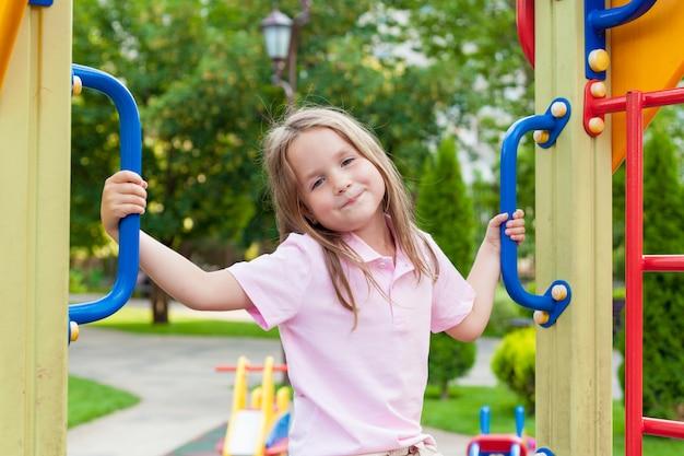 Leuk meisje dat pret op een speelplaats in openlucht in zonnige de zomerdag heeft. actieve gezonde vrijetijds- en buitensport voor kinderen.