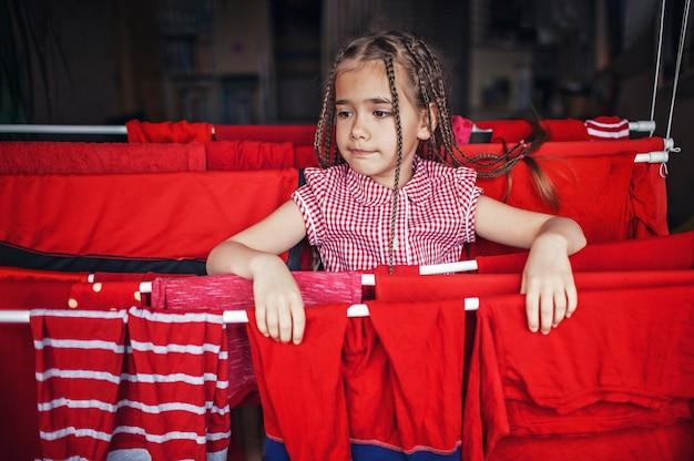 Leuk meisje dat rode kleren na het wassen helpt te hangen