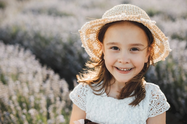 Leuk meisje dat tegen een gebied van bloem lacht die hoed en wit overhemd draagt.
