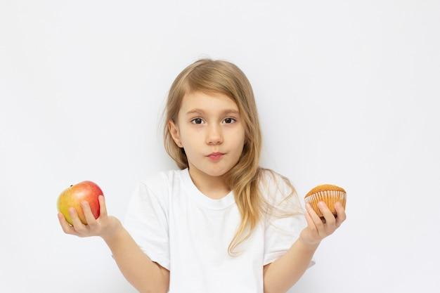 Leuk meisje dat tussen appels en snoep kiest, over wit wordt geïsoleerd
