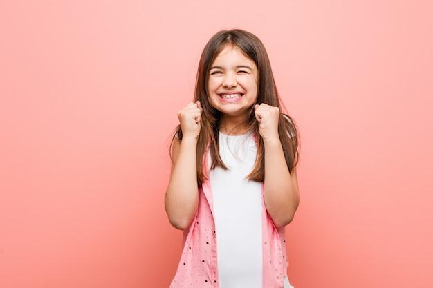 Leuk meisje dat vuist opheft, gelukkig en succesvol voelt.