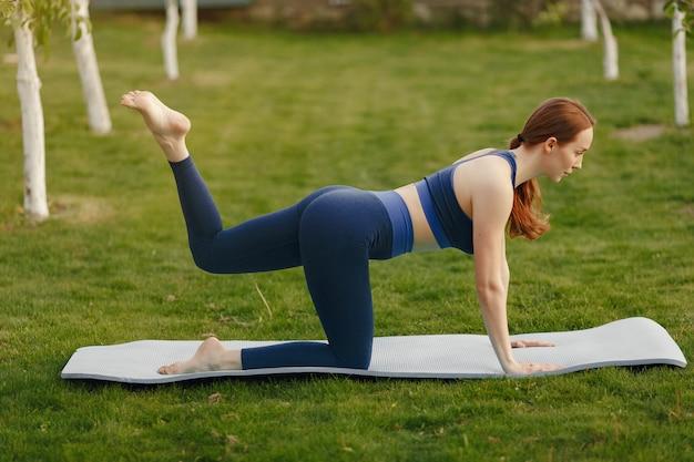 Leuk meisje dat yoga in een de zomerpark doet
