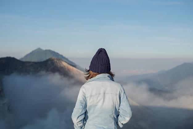 Leuk meisje dat zich achter de nevelige bergmeningen bevindt.