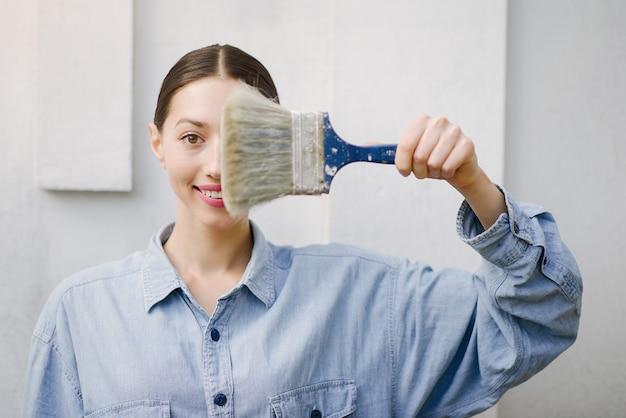 Leuk meisje dat zich dichtbij muur met reparatiehulpmiddelen bevindt