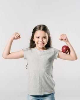 Leuk meisje dat zich met appel op bicep in studio bevindt