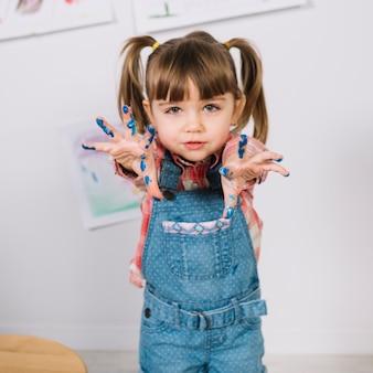 Leuk meisje dat zich met geschilderde vingers bevindt