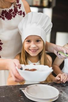 Leuk meisje die chef-kokhoed dragen die zich vooraan moeder bevinden terwijl het koken in keuken