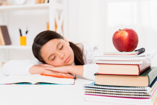 Leuk meisje die dichtbij boeken slapen