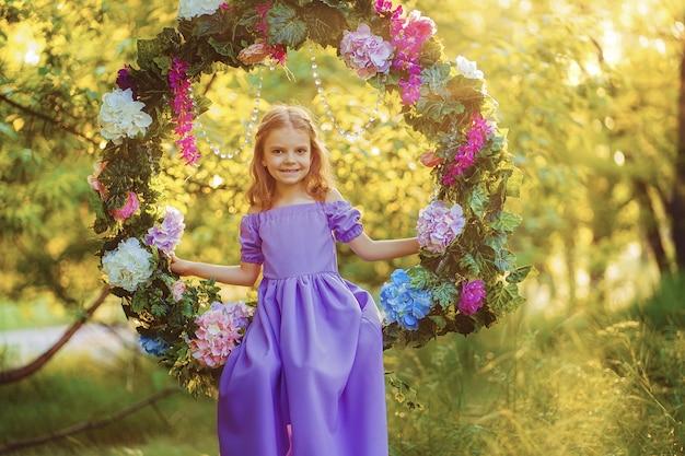 Leuk meisje die het lilac kleding stellen dragen terwijl het zitten in ring verfraaid met bloemen bij de parkzomer