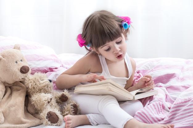 Leuk meisje die terwijl het liggen in een gezellig wit bed glimlachen