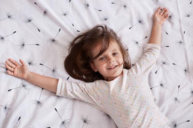 Leuk meisje die thuis spelen terwijl het liggen op deken met paardebloem op bed met slaperige en gelukkige gelaatsuitdrukking, die haar wapens uitspreiden