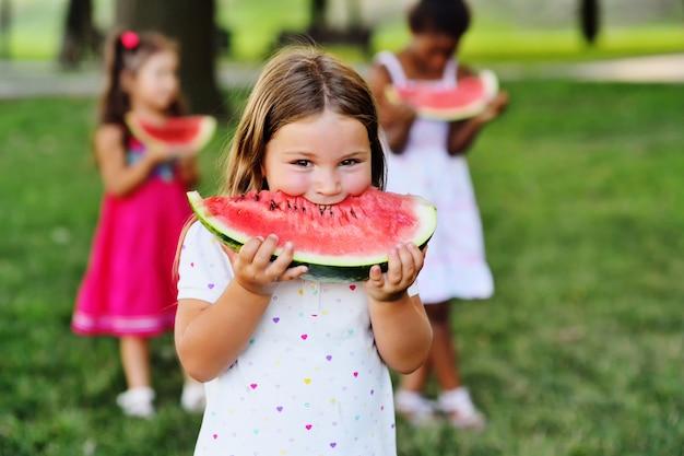Leuk meisje die watermeloen met vrienden in het park op een picknick eten