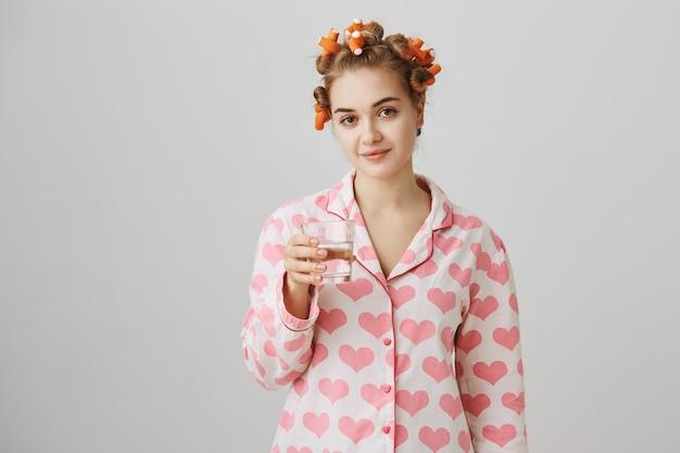 Leuk meisje drinkwater voor het slapengaan, draag pyjama's en haarkrulspelden