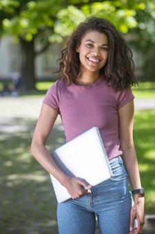 Leuk meisje. een schattig meisje in een roze t-shirt met een laptop die mooi lacht