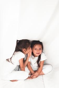 Leuk meisje fluistert iets tegen haar zus onder de dekking