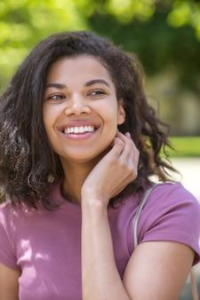 Leuk meisje. glimlachende schattige mulatta in jeans en roze t-shirt in het park