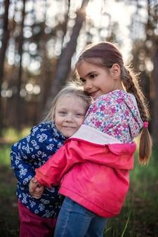 Leuk meisje haar kleine zusje met liefde en tederheid knuffelen tijdens hun wandeling in het bos op herfst, nationale knuffel- en vriendschapsdag, informele levensstijl, buiten