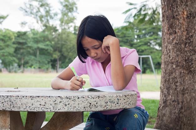 Leuk meisje het schrijven boek in de tuin