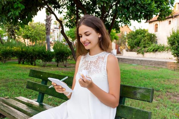 Leuk meisje houdt een pen, een blocnote en verfrommeld papier buiten op de bank